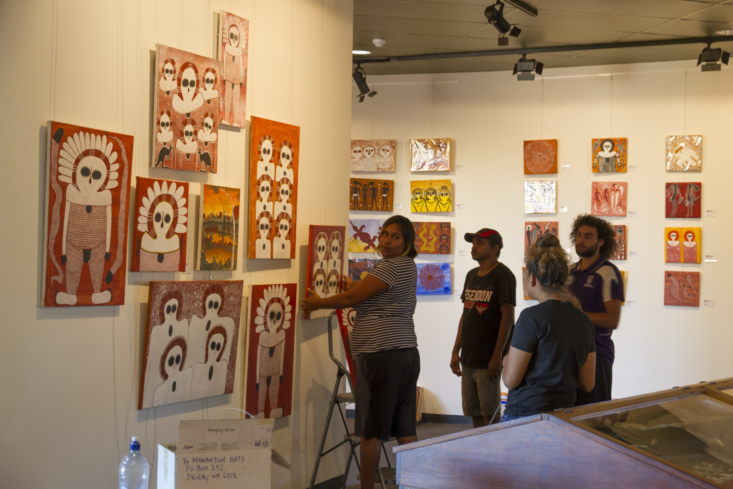 Sarah, Cissy, Stan and Dakota debating how many Wandjina's by Gordon Barunga can fit on one wall.