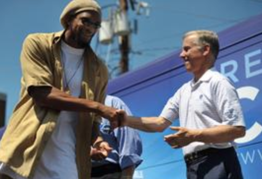 """Then-DNC Chairman Howard Dean (right) shakes hands with Etan Thomas on August 16, 2008 during a voter registration event in Alexandria, Va. Dean contributed an essay to Thomas' book """"Fatherhood."""""""