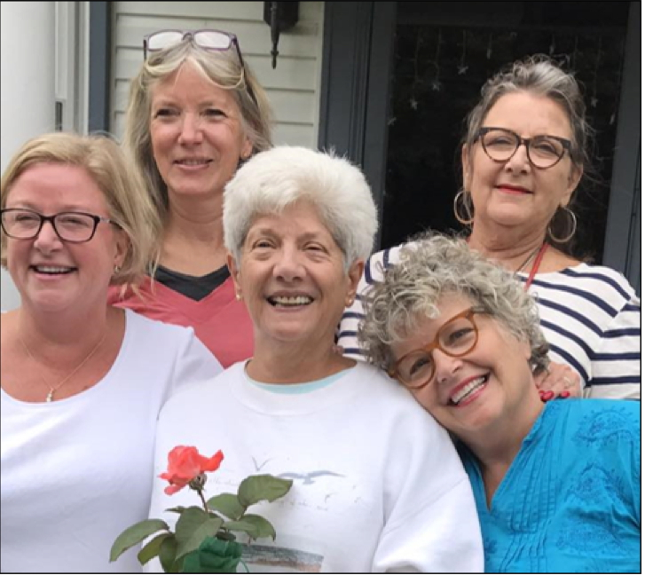 Personal DNA testing by show guest Becky Liell Hostetter (lower right, in blue) brought her into contact with her mothe'r's long-lost first daughter, Karen Gaulrapp (center, with rose), who was given up for adoption in 1946. In this photo, Becky, Karen, and the three sisters Becky grew up with (left to right, Kitty Liell, Maggy Liell and Nora Liell) spend a recent holiday weekend together.