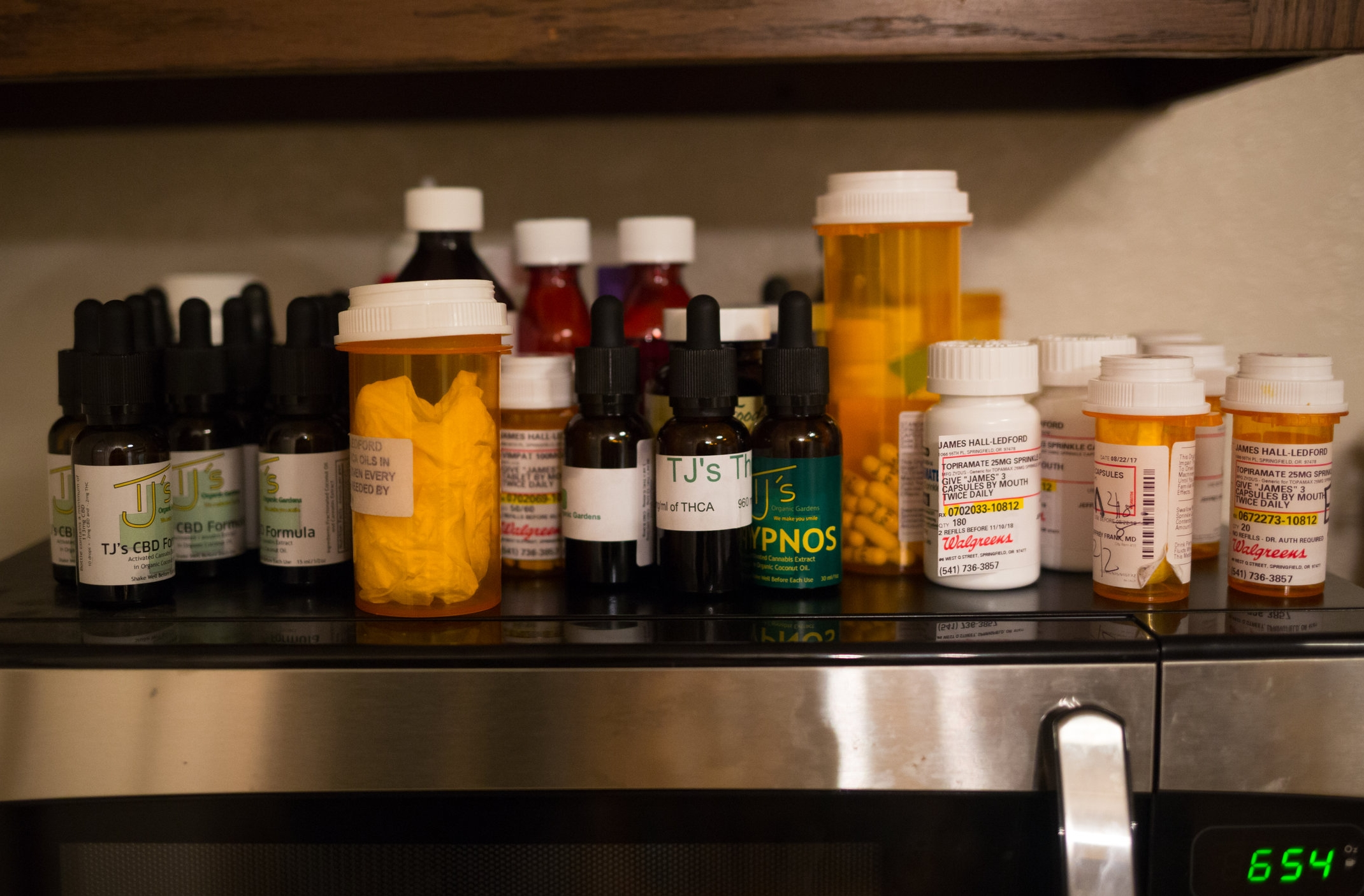 A various combination of pharmaceutical and cannabis derived medicines above the kitchen microwave. James is still not entirely pharm-free. He remains on a low dose of his former prescribed treatment along with the CBD, THC and THCA oils.