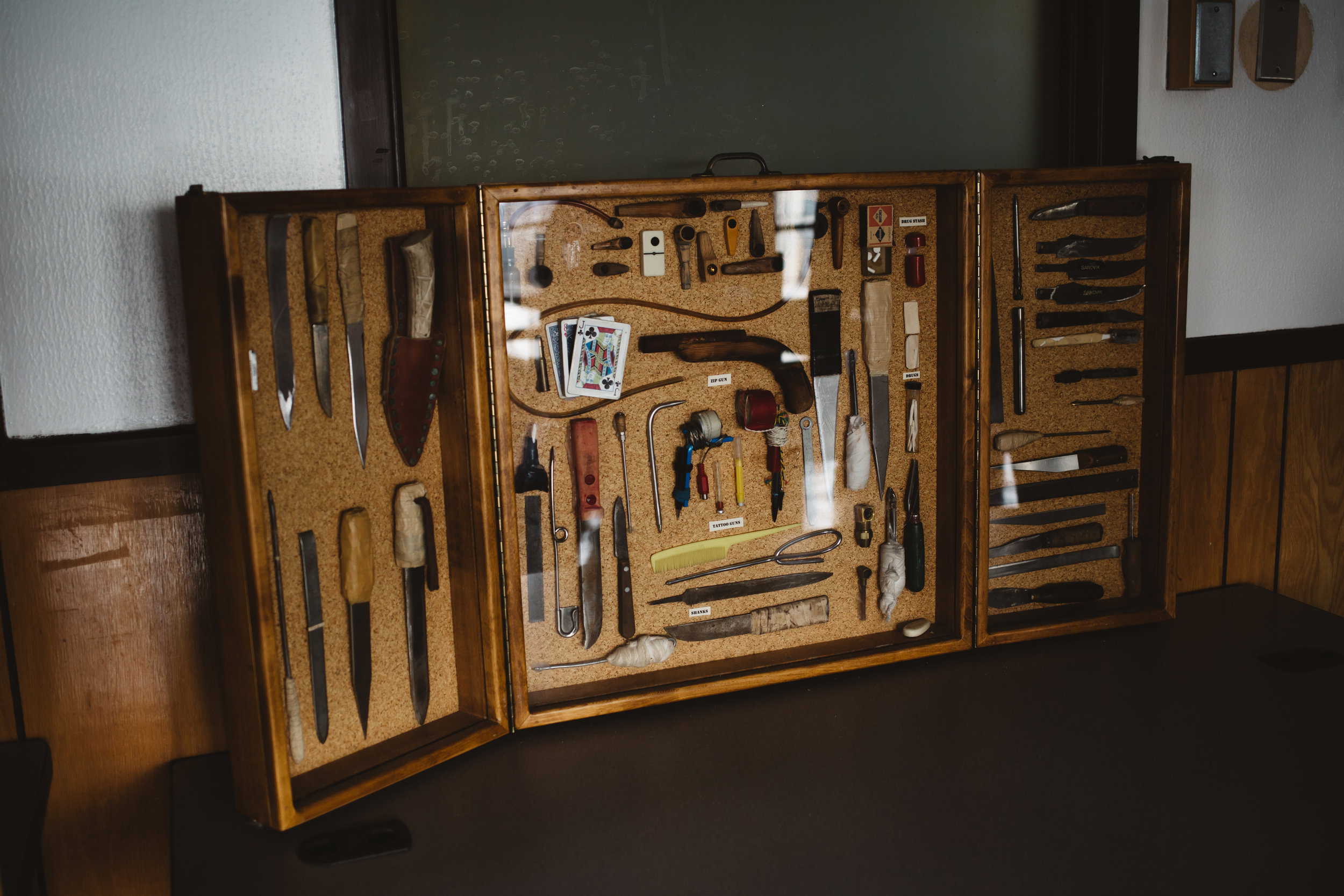 "A display case shows a varierty of confiscated contriban found in cells throughout the prison. After his lengthy shifts ended, Ashley attempted to leave work at the prison when he went home at night. But the daily stresses of his job had made their way into his home life. ""When you're working in a negative environment like a prison setting, what happens is you start creating these firm boundaries, and sometimes you take those boundaries outside of work. You start having these expectations, you stop trusting people and you can find yourself being really isolated"", Ashley said."