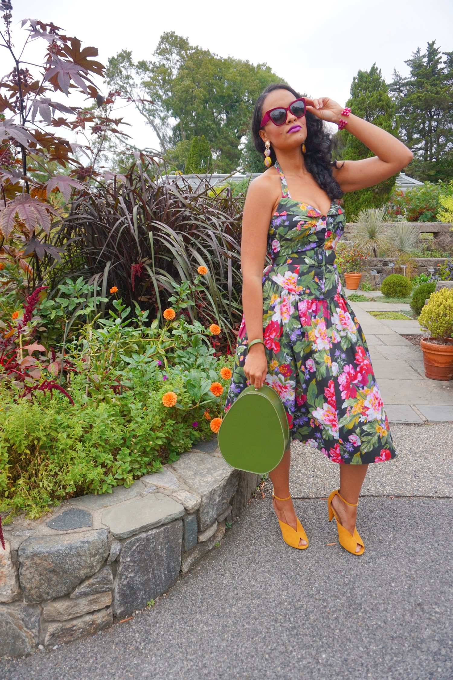 Mixing the decades - Krystle styles a 50s vintage floral halter dress with 40s inspired modern heels in a mustard color, tiered fabric button earrings, velvet sunnies in a deep wine color, and vintage beaded bracelet in purple that belonged to her mom. A vintage train case in an avocado green serves as her purse. <3