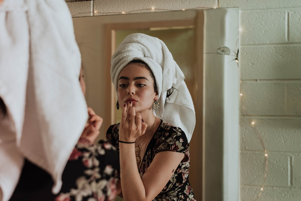 Woman applies make up in the mirror.jpg