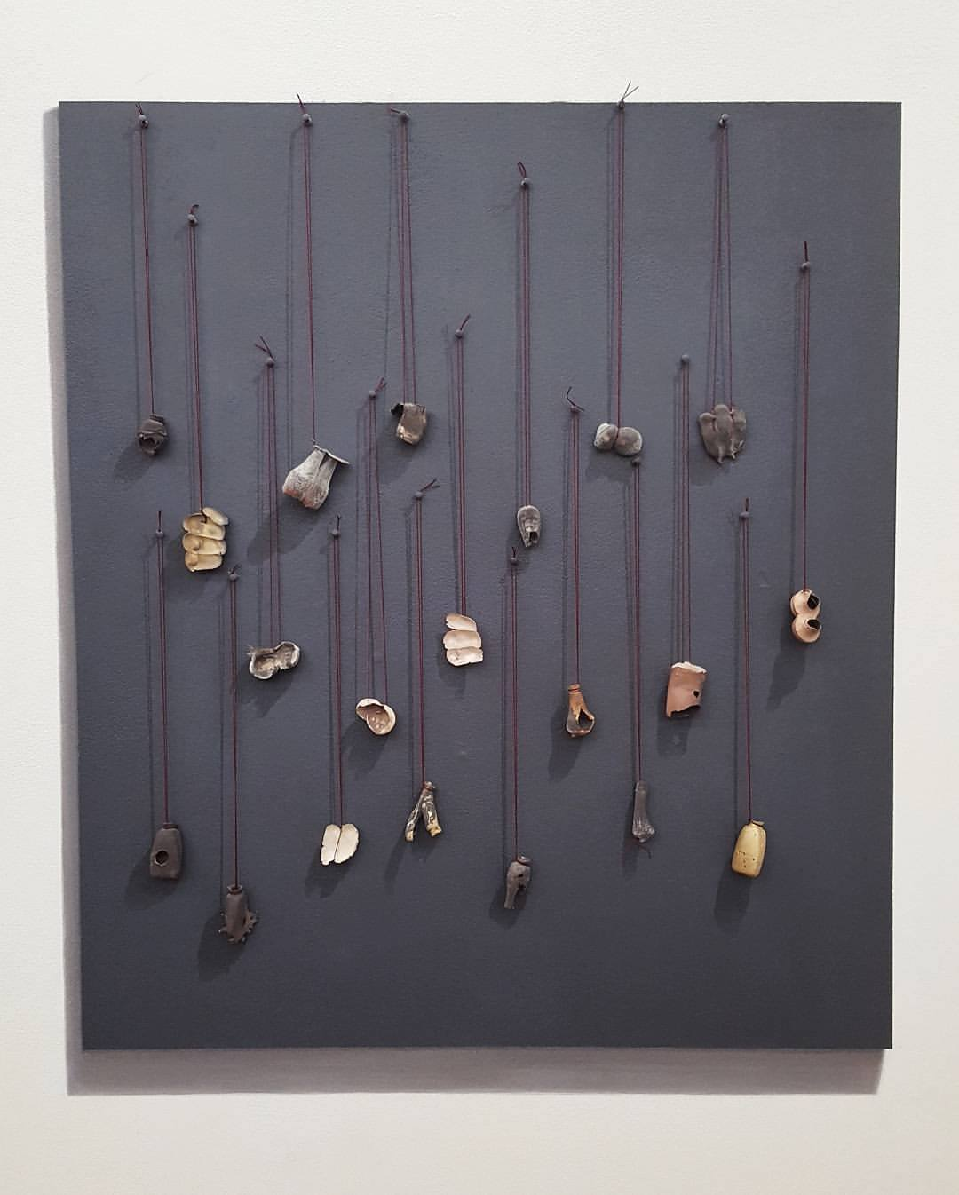 """Trompe l'oeil painted wall display for pendants by  MJ Tyson   (shadows, and backing board are painted on a white wall"""")"""