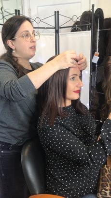 Gitel fitting a customer for a wig