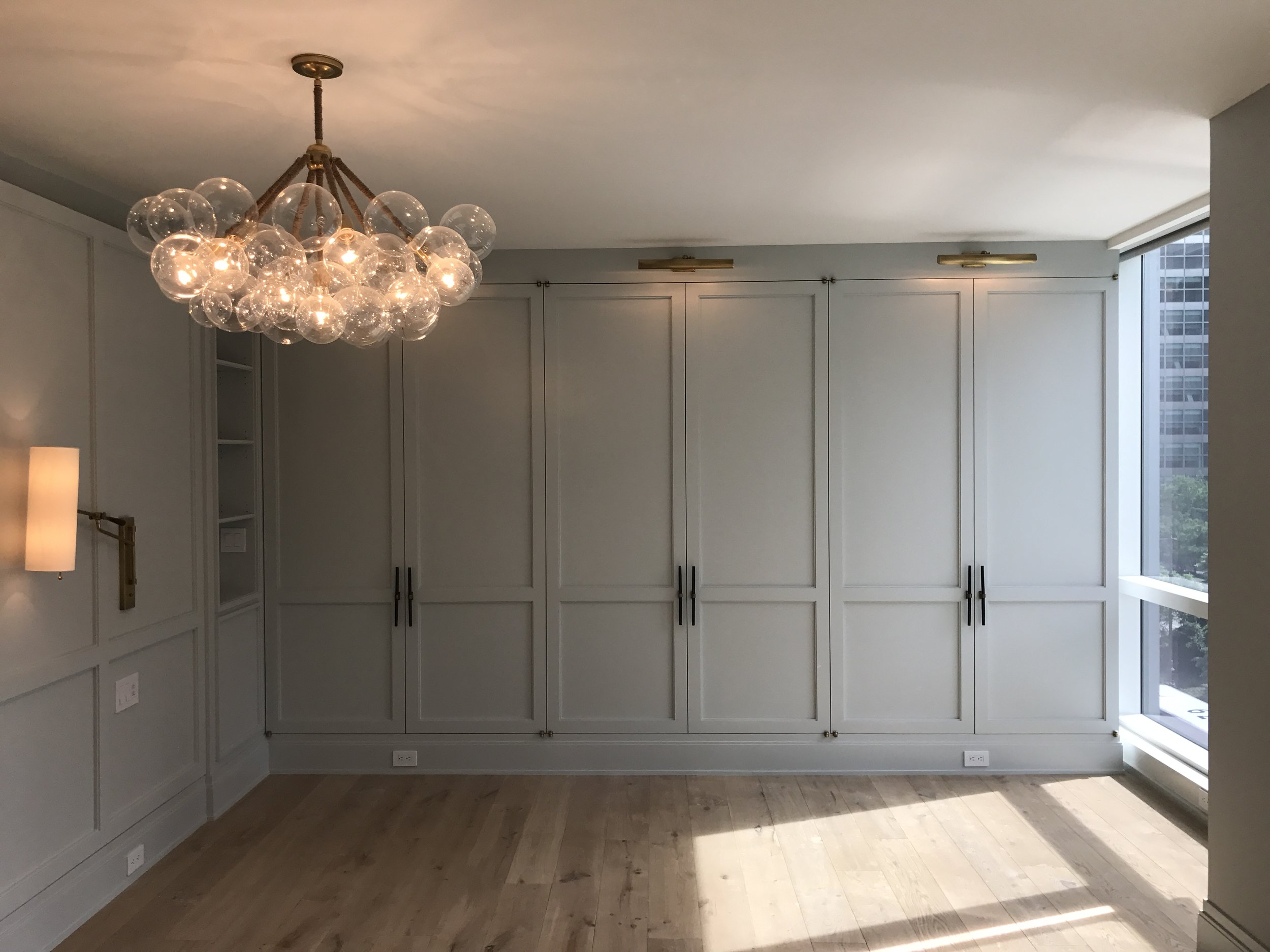 Paneled beautifully with an offset design, beautiful horn hardware for the wall of custom closets, painted in Skylight from Farrow and Ball, sconces in antique brass and linen and chandelier inspired by Pelle.
