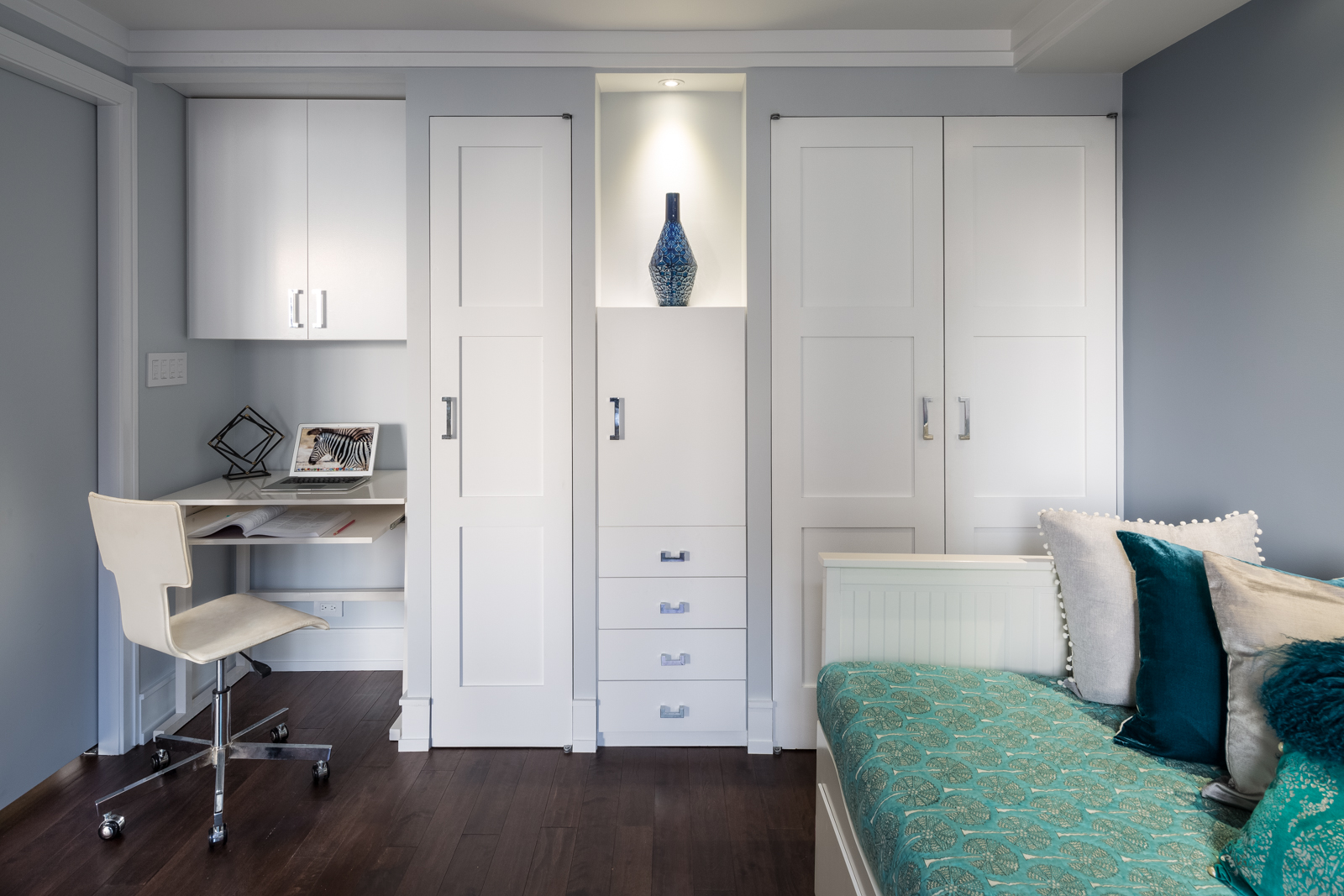 We designed a custom niche for the desk and created additional storage in the room. The pocket doors provide much needed privacy when needed to the room which otherwise is intended to be mostly open. These closets hide the pipes in the middle and we designed a spotlight to highlight the niche. We live for such design solutions!!