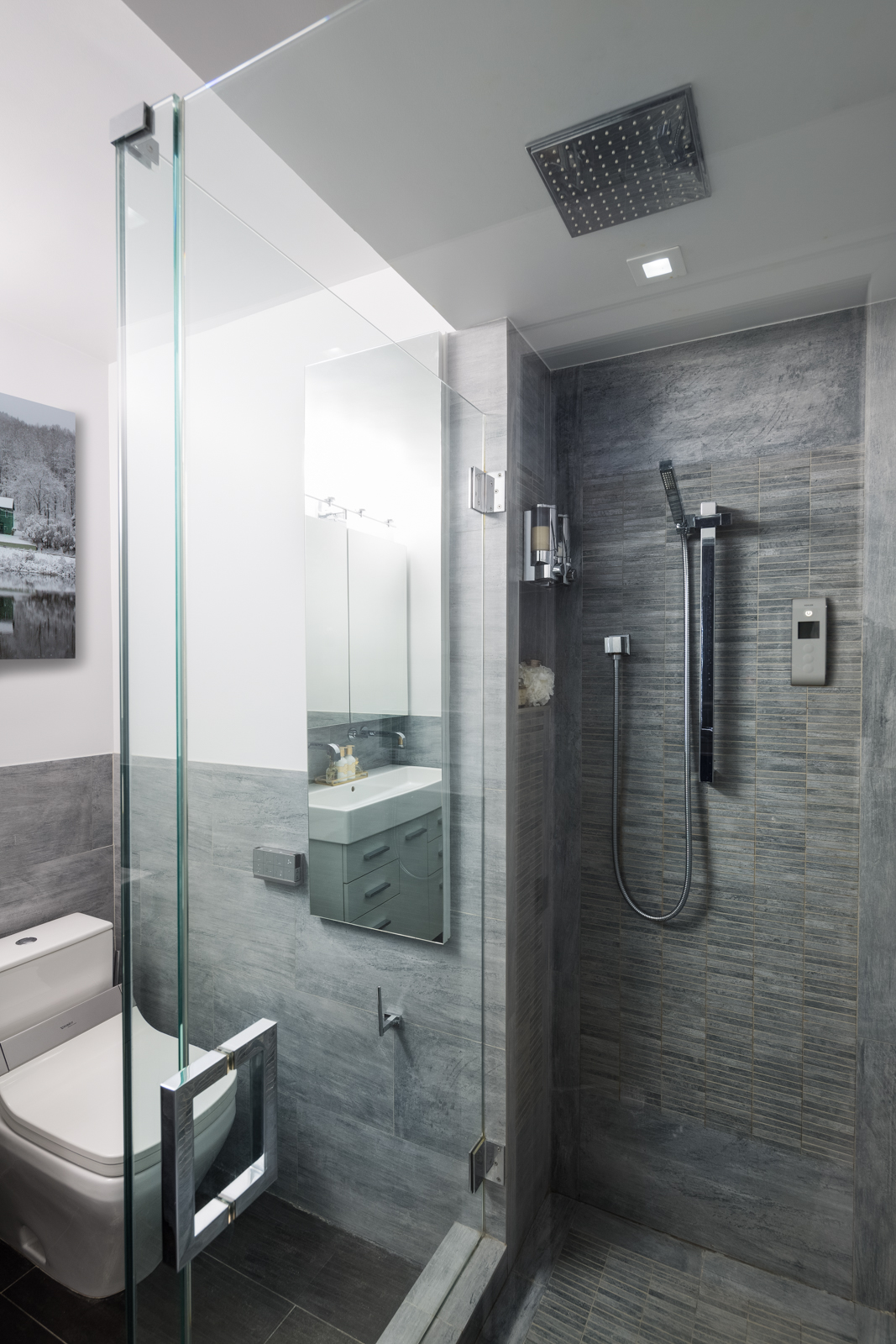 The standing shower has glass on 2 sides and feels open and airy. Polished chrome fixtures from Grohe and the large overhead rainshower creates a great bath experience. The built in niche tucked away on the side is a necessity with all the products!
