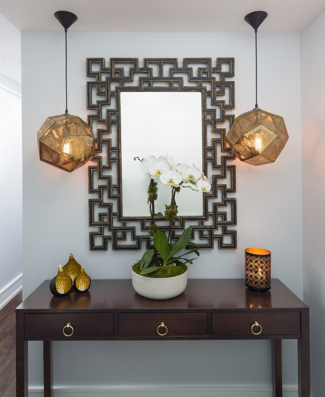 This entry foyer is perfection. The orchid in the middle of the mirror flanked by the pendant lights creates a playful organic symmetry. The white base breaks the darkness of the console table and adds a welcome contrast.