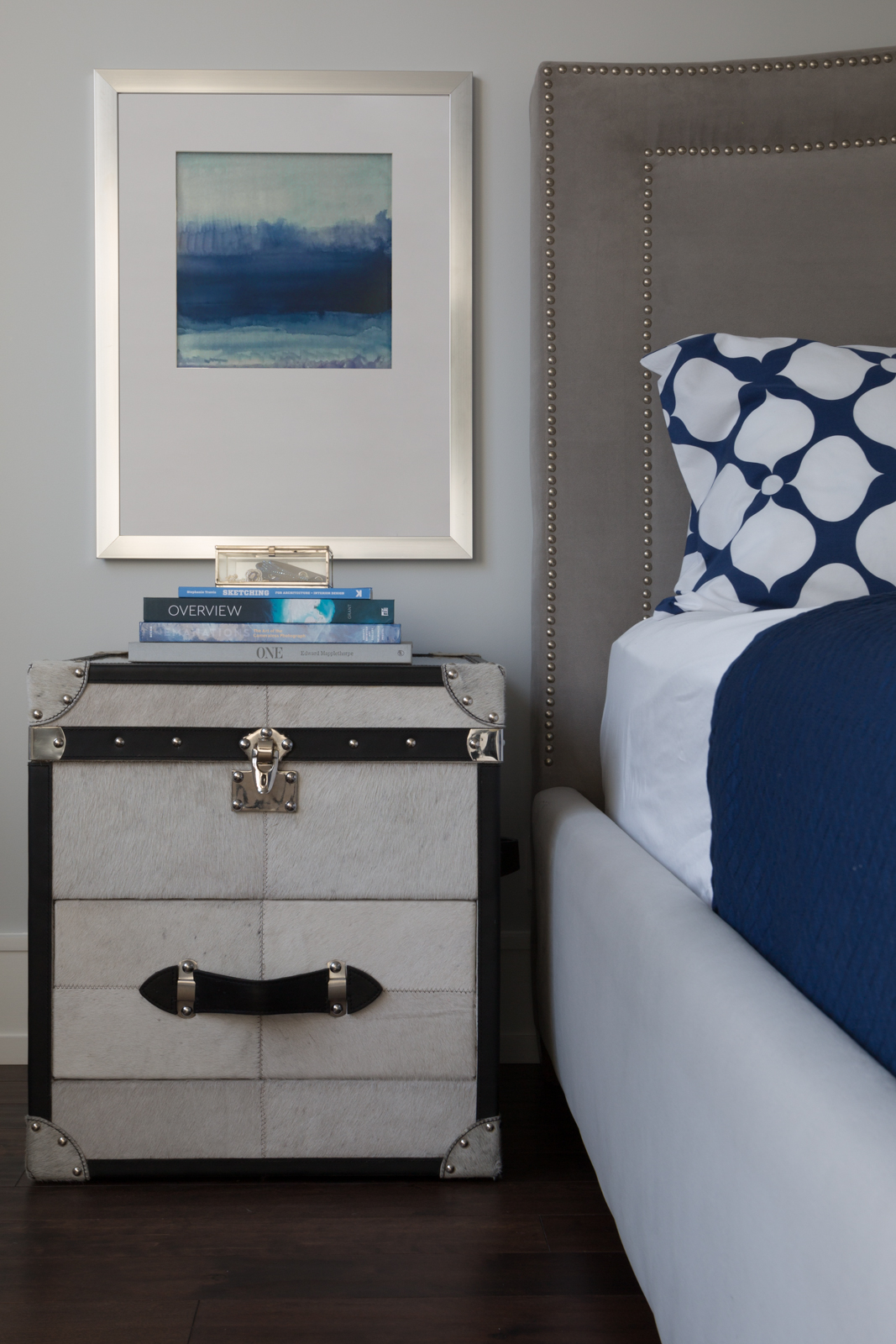 Detailed styling shot of this master bedroom. There are so many interconnected details in this shot. The nail head trim on the nightstand, nail head trim on the bed and the silver frame. The blue from the bedding interacts with the blue books, artwork and blue jewelry in the display box. The black leather and the white bedding create an accent.