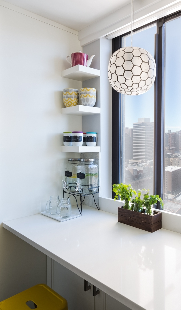 Styling these open shelves, I had a problem of plenty. The homeowner had these lovely grey and yellow bowl which I placed in the middle shelf to bring out the yellow from the stool. The fresh herbs from her home garden add freshness in an indoor New York kitchen,while the jars with the colorful lids and chalkboard labels are playful and enhance the black window frame.