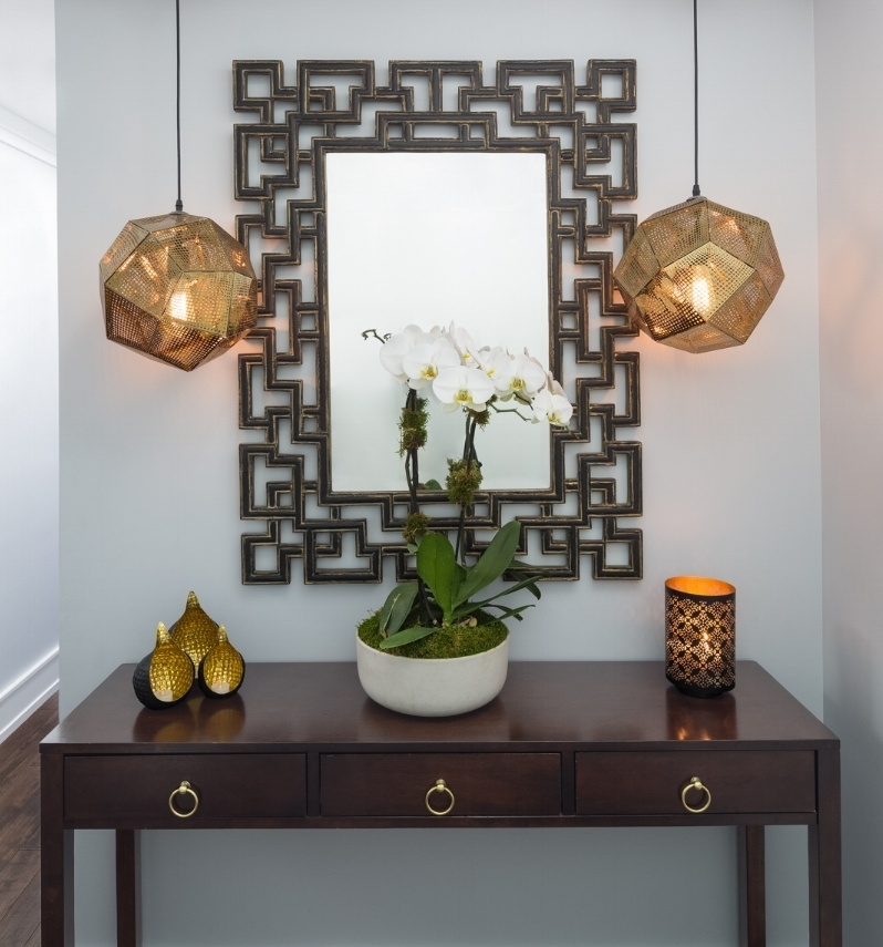 What a stunning entrance as soon as you walk in!The existing mirror was our inspiration piece and we built in feature pendant lights to create an entry that made a statement. We offset the warmth of the mirror and lights with neutral grey painted walls. Fresh flowers always bring in the softness.
