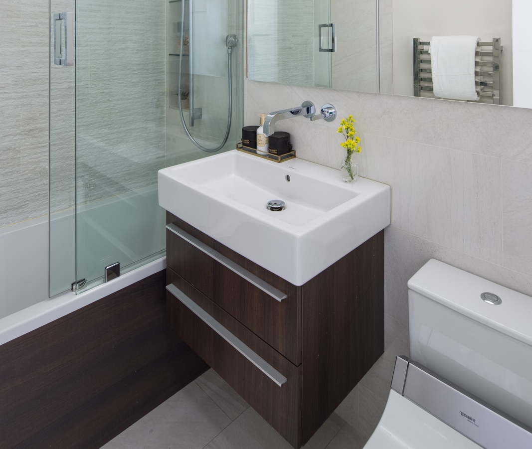 Oftentimes in New York, we are given the challenge of a typical 5'x7' bathroom and we make it special by choice of material and finishes. Wanting to create a modern bathroom with a rich material choice, we chose a walnut veneer for the floating vanity and the tub apron to contrast with the travertine-looking porcelain tile. The feature wall is a linear textured porcelain tile in the same color. Adding a barn style glass door for the tub shower combo makes the room feel larger. Wall mounted vanity faucet in polished chrome over a furniture sink adds to a modern decluttered vanity instantly. I love using furniture sinks. Not to miss, the toilet (which can never be a design feature) has a heated seat and bidet with all the bells and whistles one can imagine.