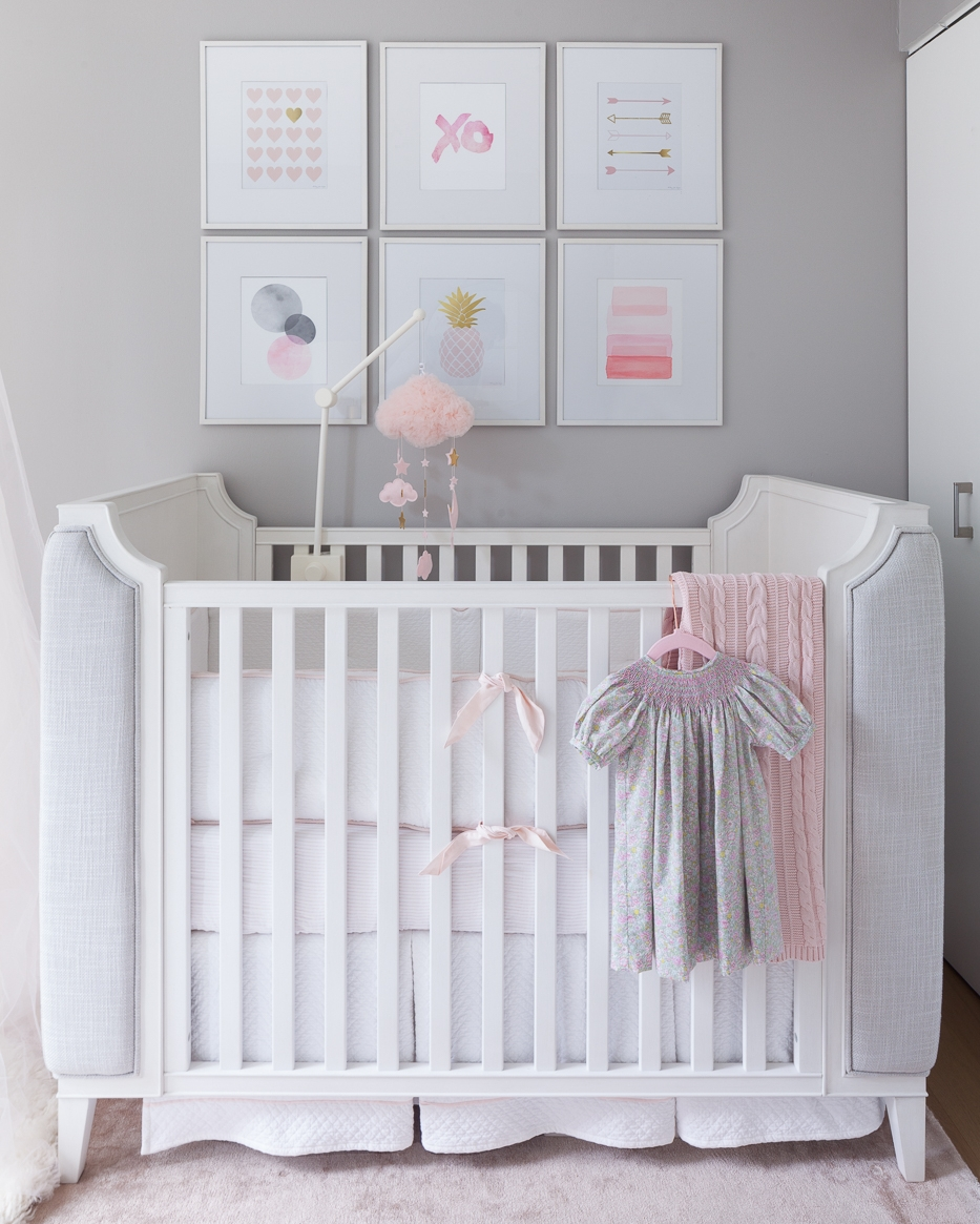 I loved designing and styling this nursery. I added a blush knitted blanket on one side of the crib to create some weight in an otherwise very ligth and fluffy room. The dress in front hangs on a pink velvet haner with rose gold metal. I could have picked a pink dress (which every mom has for her baby girl) but instead I chose this floral green dress with a smoking neck to break the color a bit. I love the symmetry of this picture and the styling enhances it a few notches.