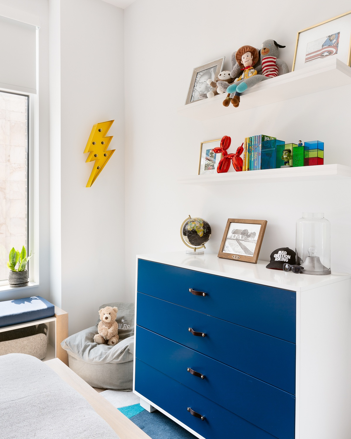Beautiful custom dresser with leather pulls create much needed storage and style on the other side of the room against a simple painted wall. The accent lightning bolt marquee light brings the super-hero theme and floating shelves above create space for rotating gallery of art, toys and of course books. Felt baskets provide easy access to toys, blankets and more books for our little reader.