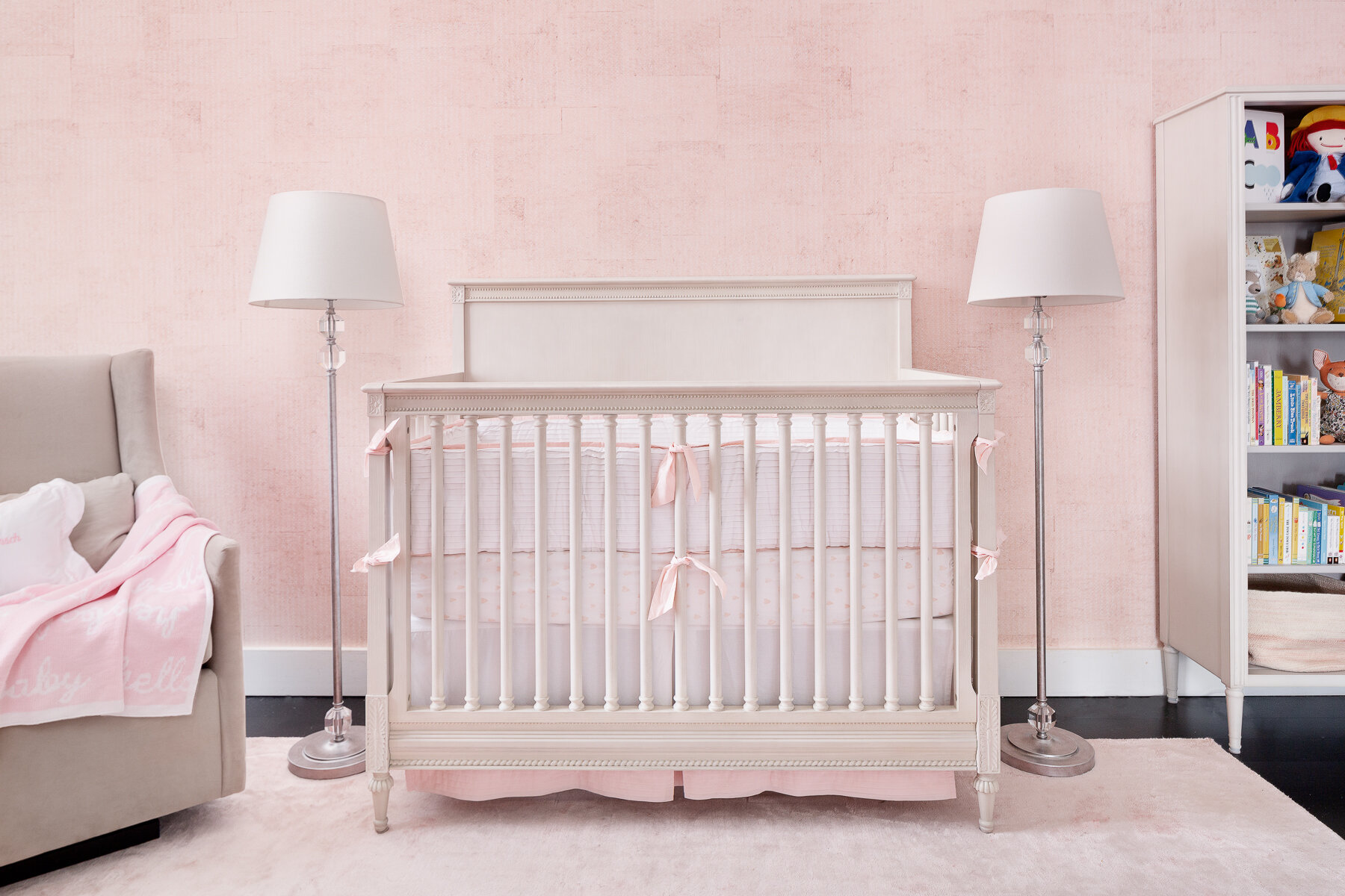 And here is the nursery for their first born baby girl. She is as delicate and the real jewel in this room. The beautiful texturral wallpaper gives a hand plastered background to the room. This room was hufe for a nursery and we made it cozy by flanking the crib by two floor lamps and selecting a crib with a headdboard. The details of the beautifully crafted crib and its wormanship complemented by the wallpaper and the pintucked detail on bumper, all create a sophisticated collected room.
