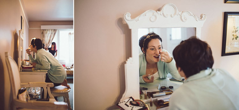 Bride putting on makeup in bridal suite