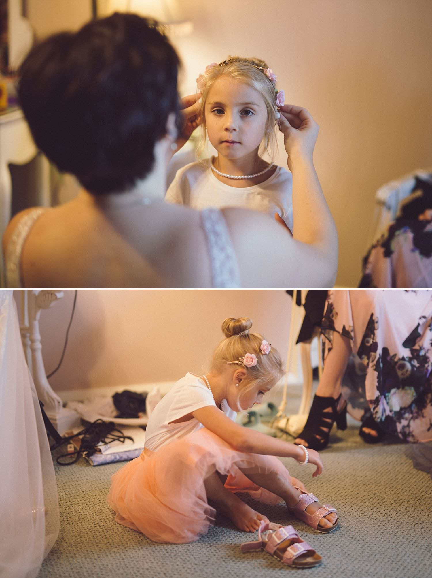 Bride fixing flowergirl's hair, putting little shoes on