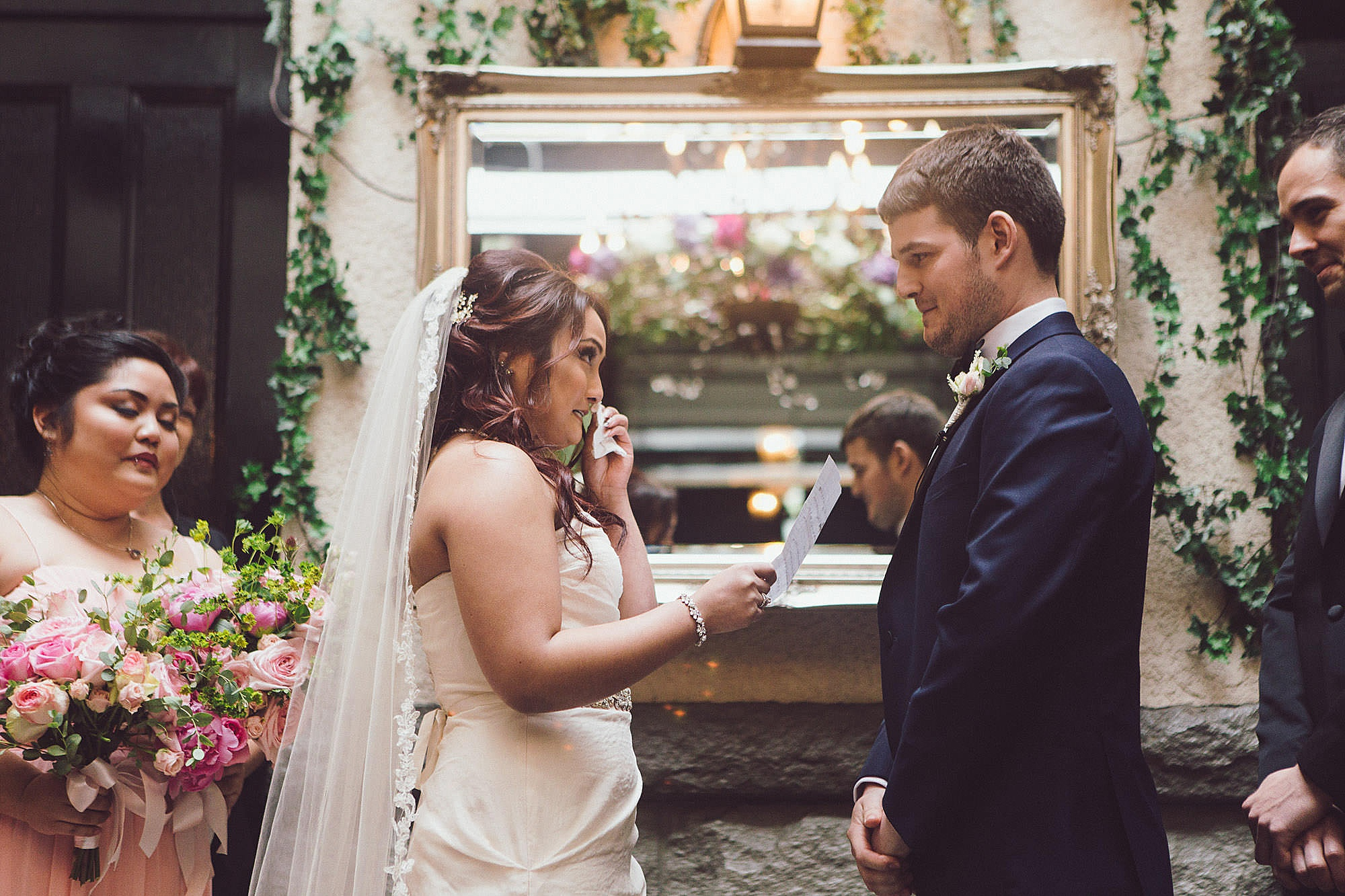 Bride wipes away a tea while reading vows
