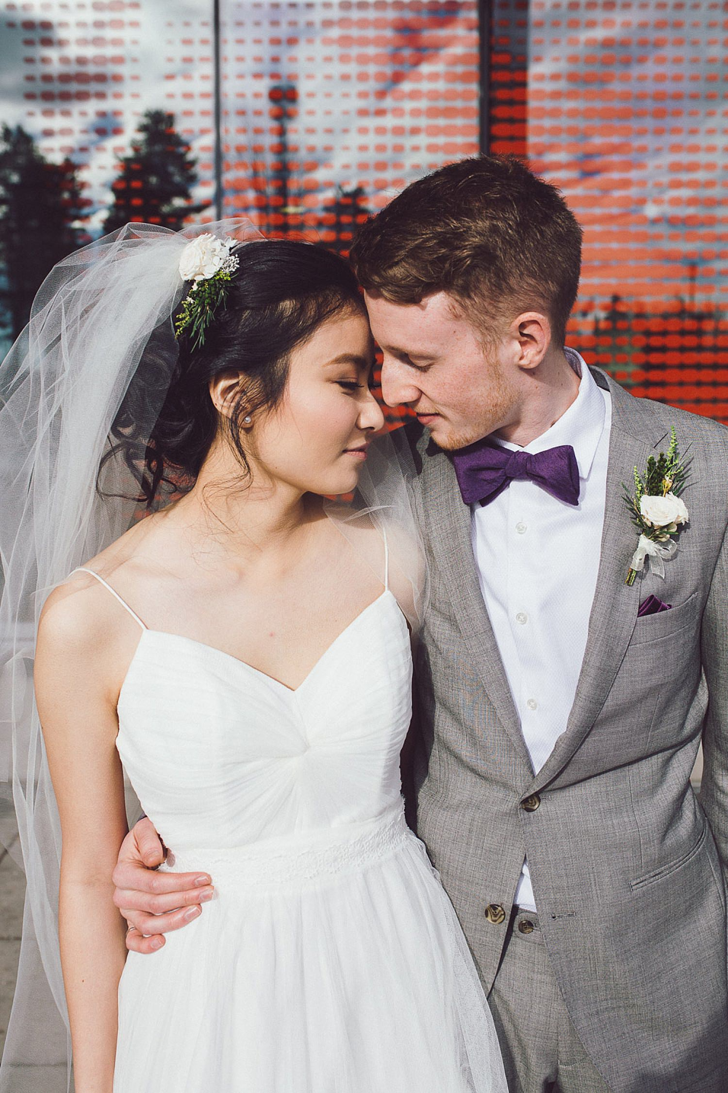 Bride and Groom get close in front of Blusson Hall at SFU