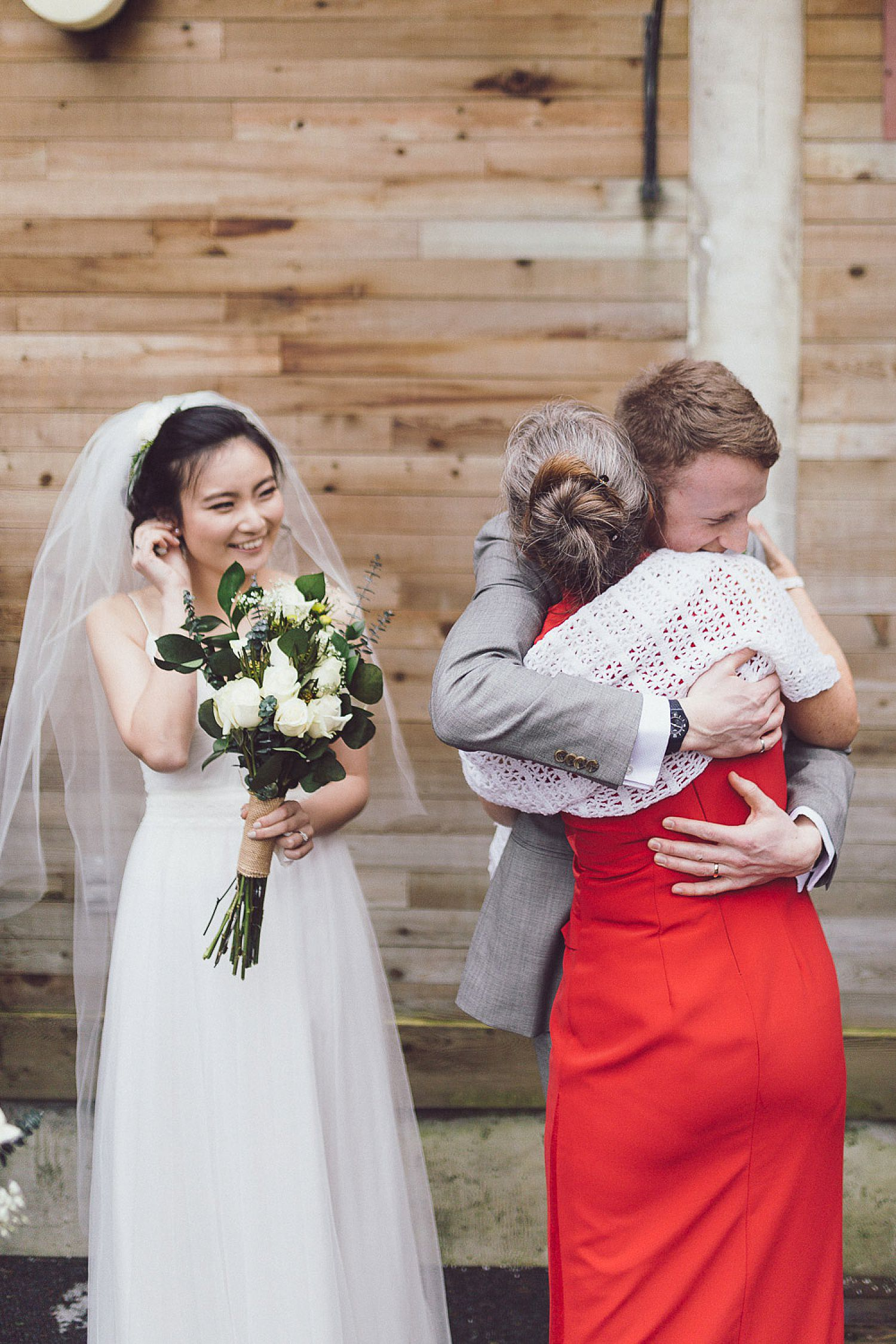Mom gives bride and groom a hug