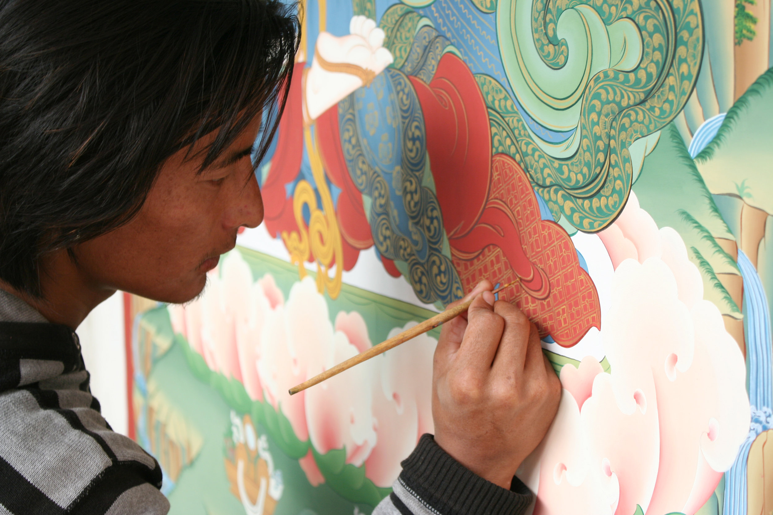 Sonam Rinzin inking details on cloth with gold paint.
