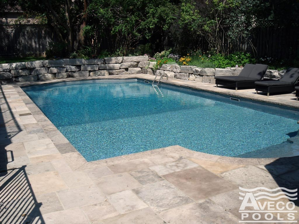 Lounge Chairs Beside Swimming Pool With Stone Deck