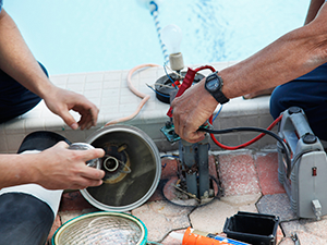 Men working together on a swimming pool equipment