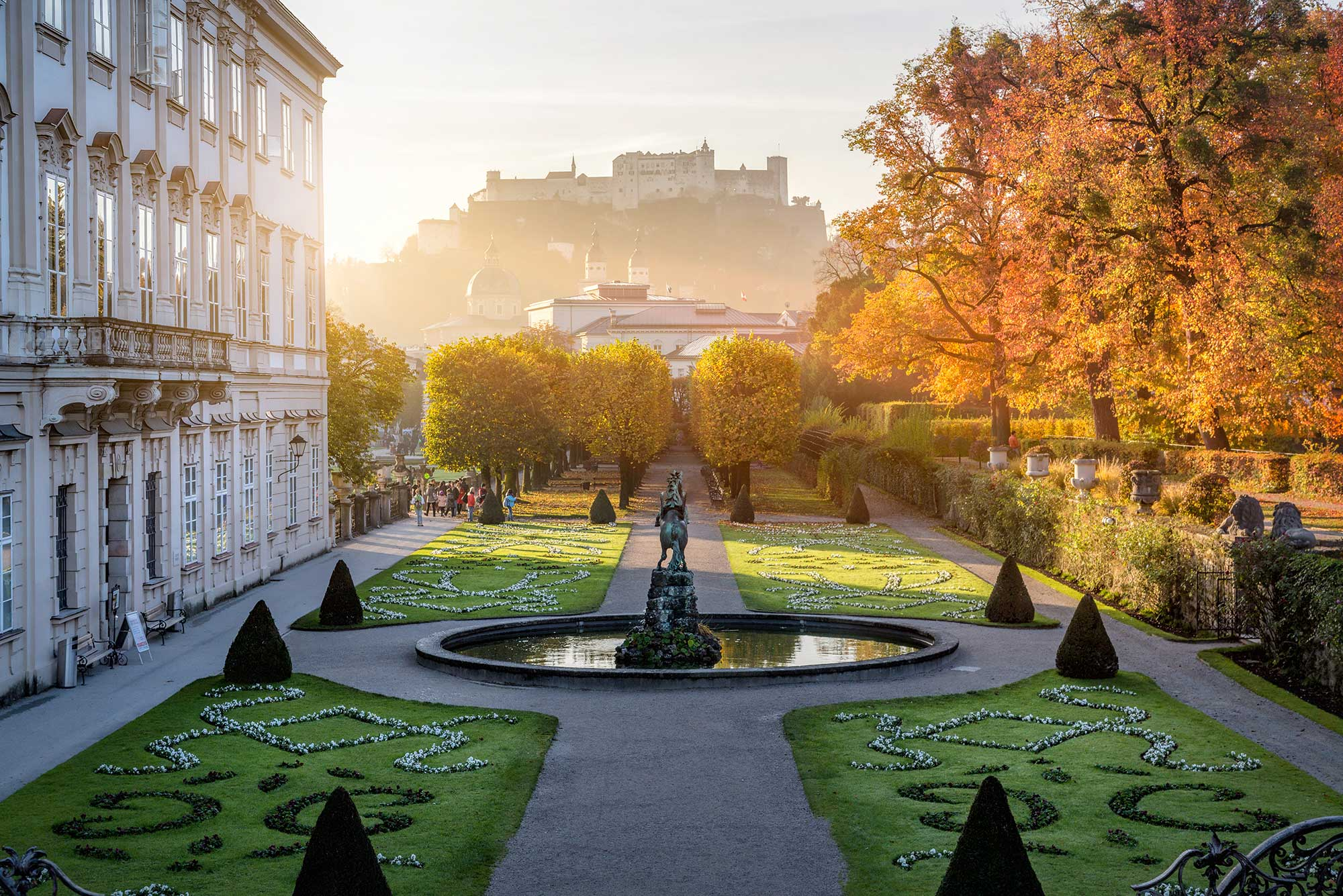 The gardens of Mirabell Palace and Hohensalzburg Fortress in the distance at sunrise.