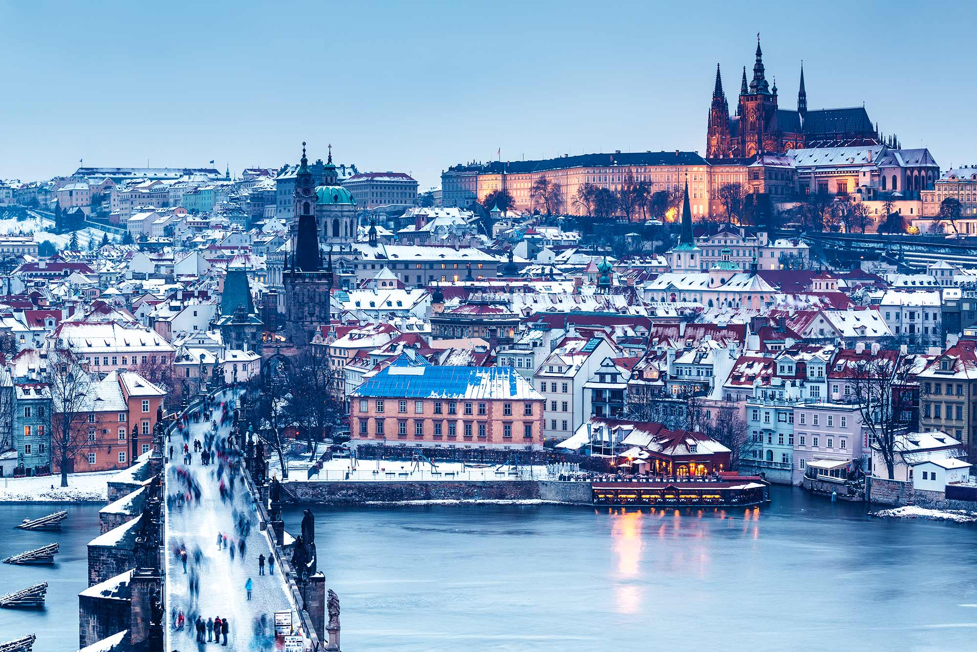 A wintery scene in Prague with the Charles Bridge and Prague Castle in the background.