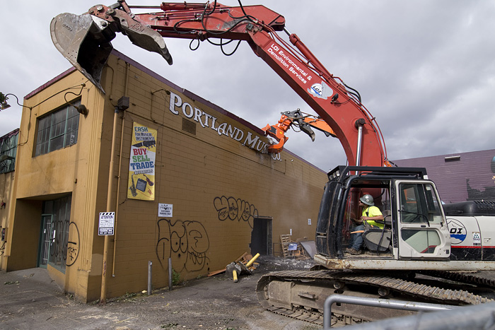 Kyle Berens uses an excavator to support the building as the demolition of the structure begins.