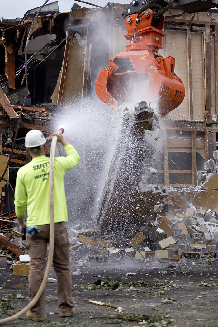Jake Wagner sprays to contain dust as the structure is brought down.