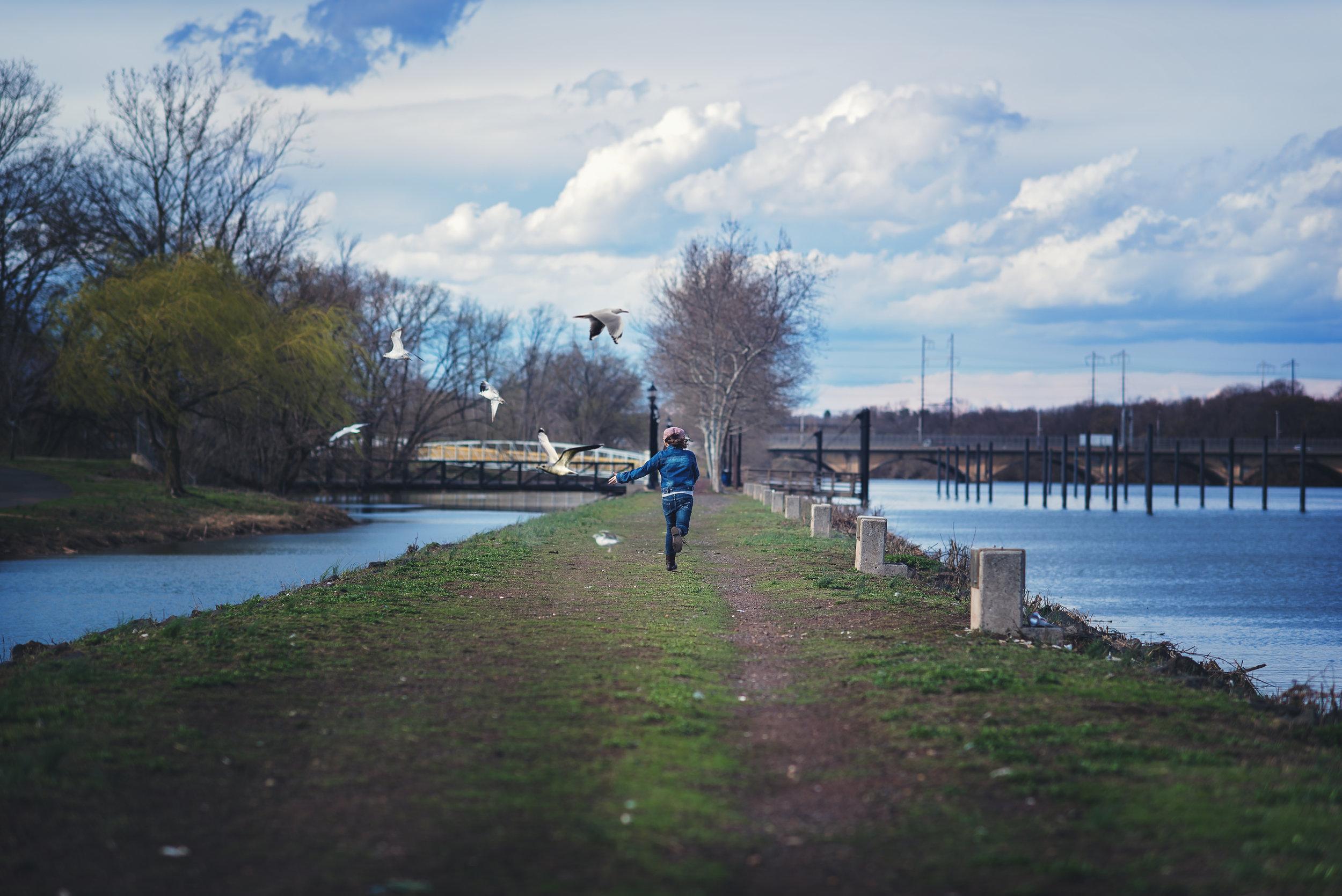 Girls running away with seagulls