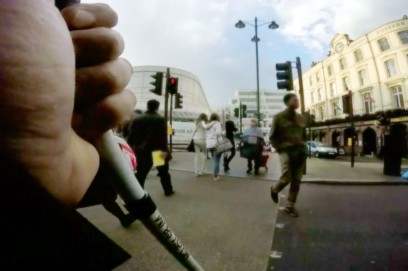 Close up of research participant's hand holding white cane standing at a pelican crossing in daylight.