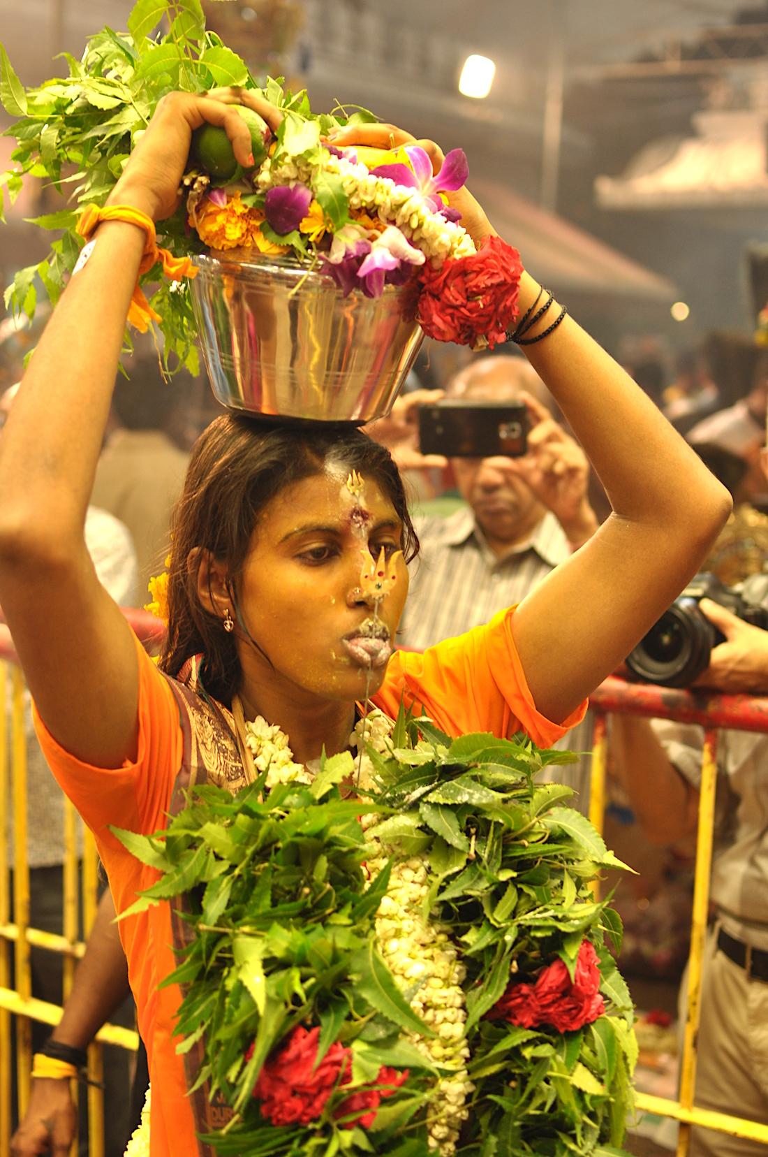 Mulher com agulha na língua. O balde de leite na cabeça é uma oferenda. Foto: Patti Neves