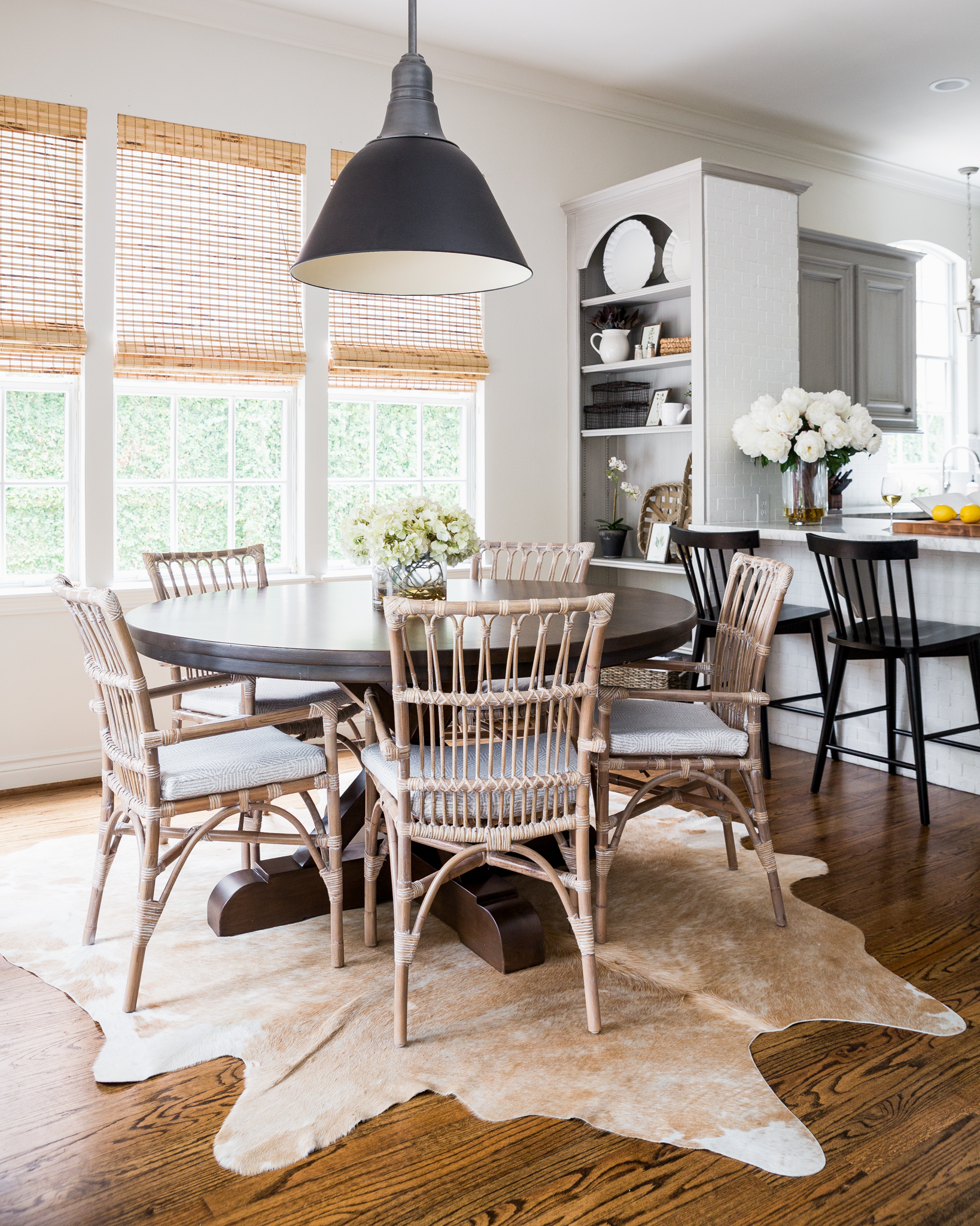 Farmhouse Breakfast Room with Cowhide Rug and Rattan Chairs.jpg