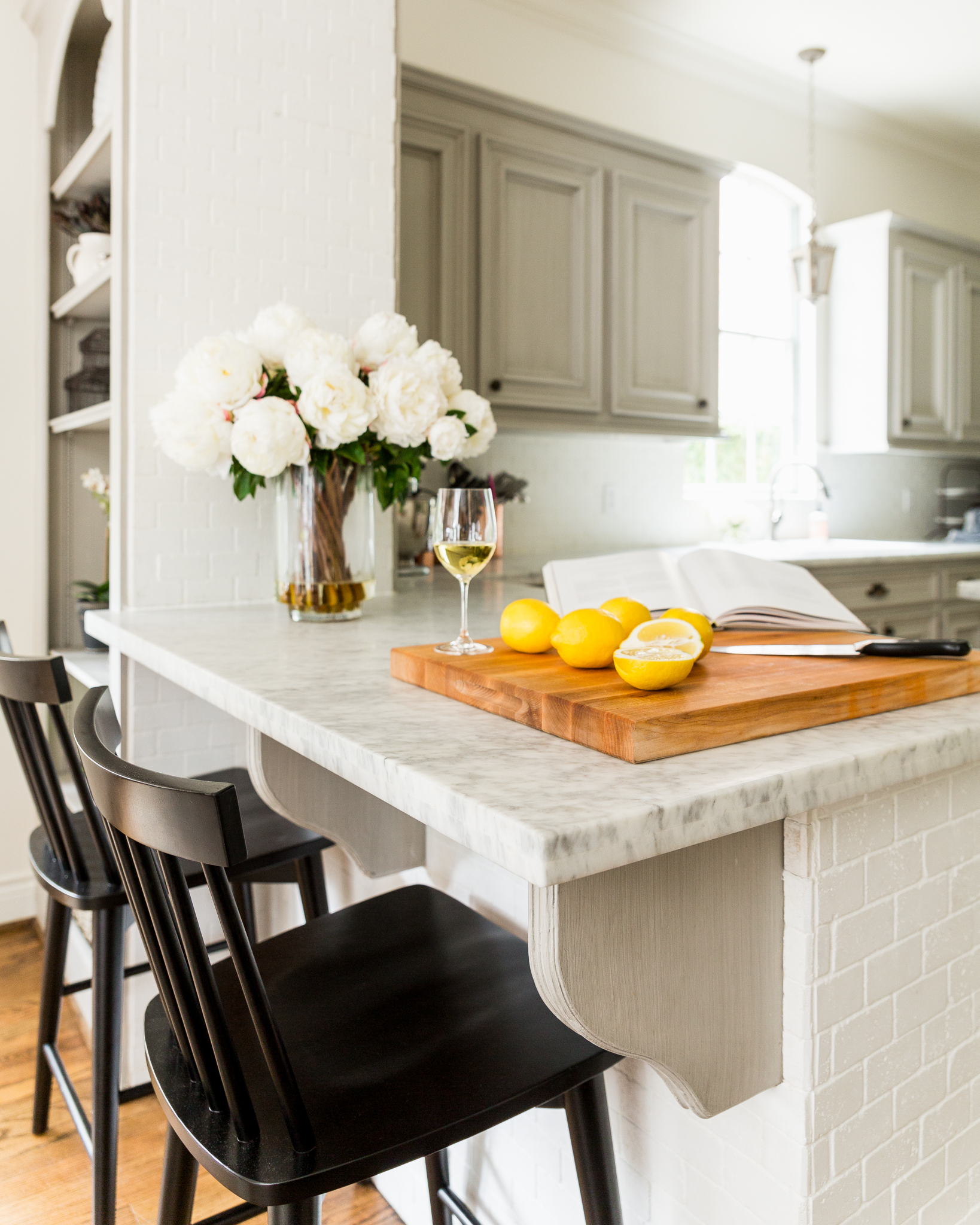 Black windsor chairs in white marble and grey cabinets kitchen
