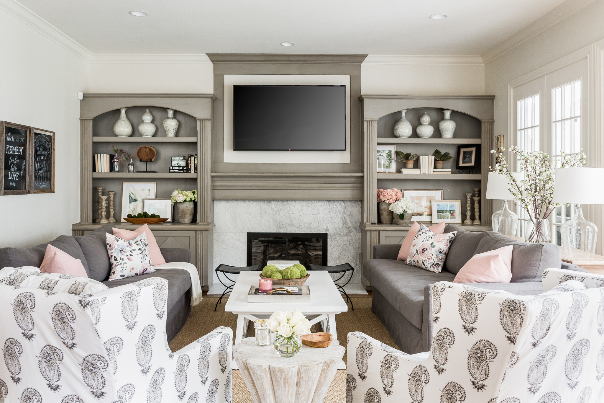 Bright Family Room with Two Gray Sofas and Patterned Swivel Chairs