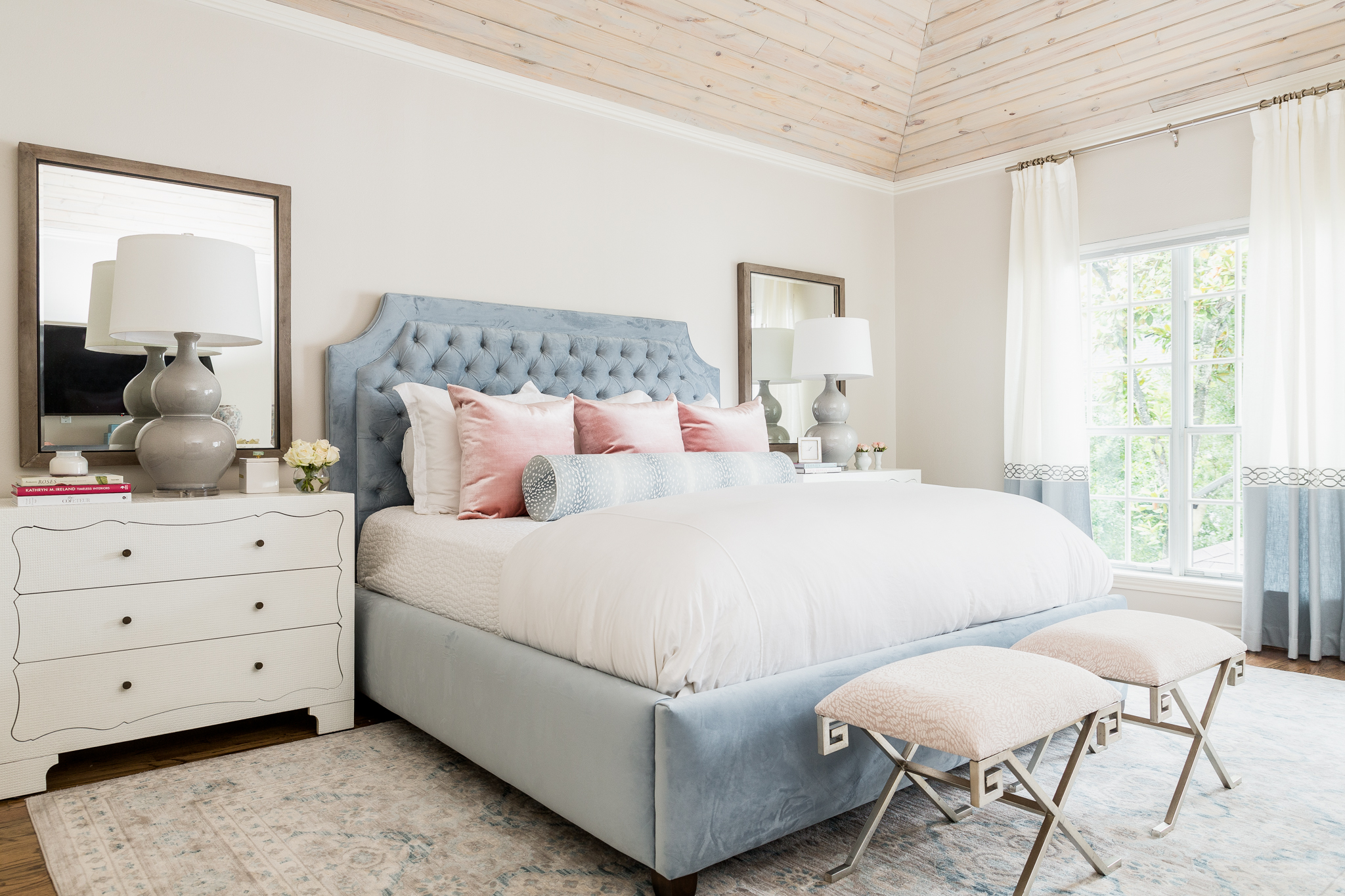 Master Bedroom with blue tufted headboard and high ceilings