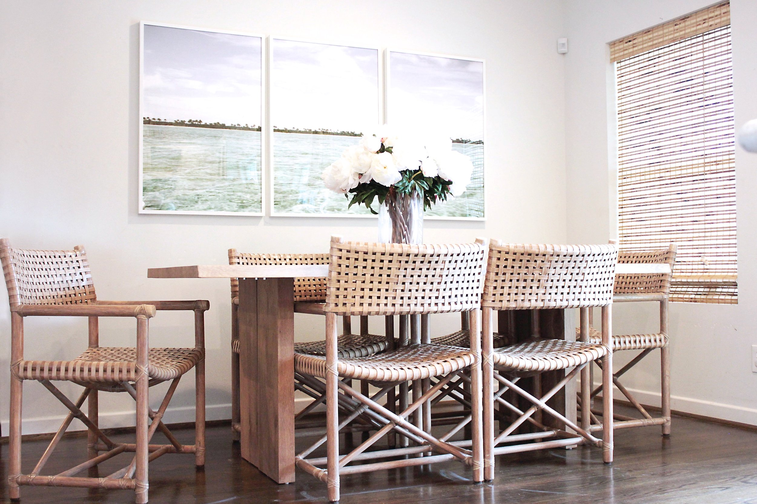 Bright dining room with light oak table woven blinds and rattan chairs