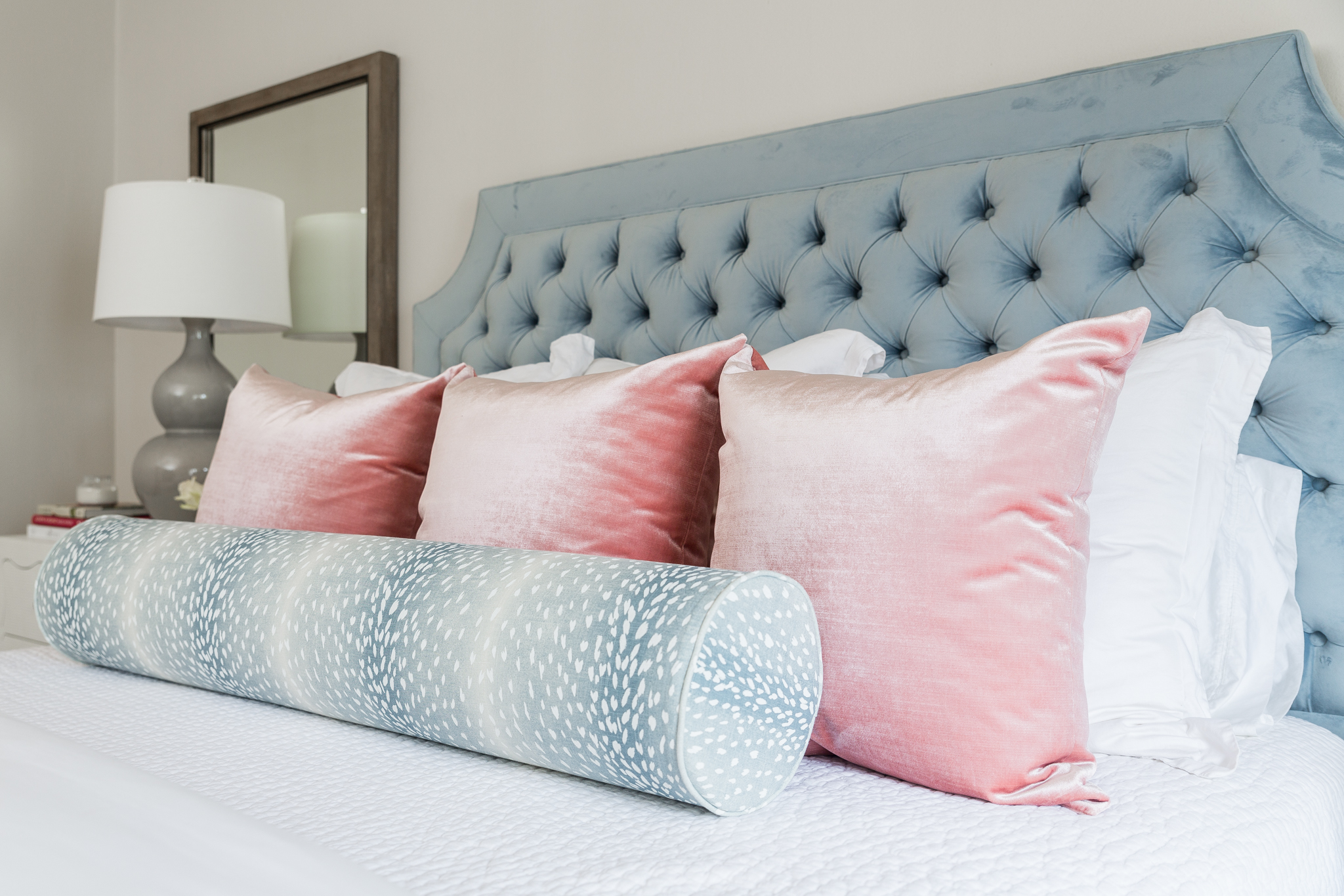 Blue tufted bed with pink pillows and antelope bolster pillow