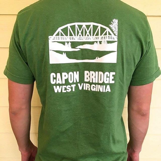 REMINDER: Today is our T-shirt Pop Up SALE -- at The River House! . From 9 AM to 2:30 pm, come get your CAPON BRIDGE t-shirt for $20 ($10 goes to local charities). . Etched glasses and framed posters are also up for grabs! . #visitcaponbridge #shoplocal #townpride
