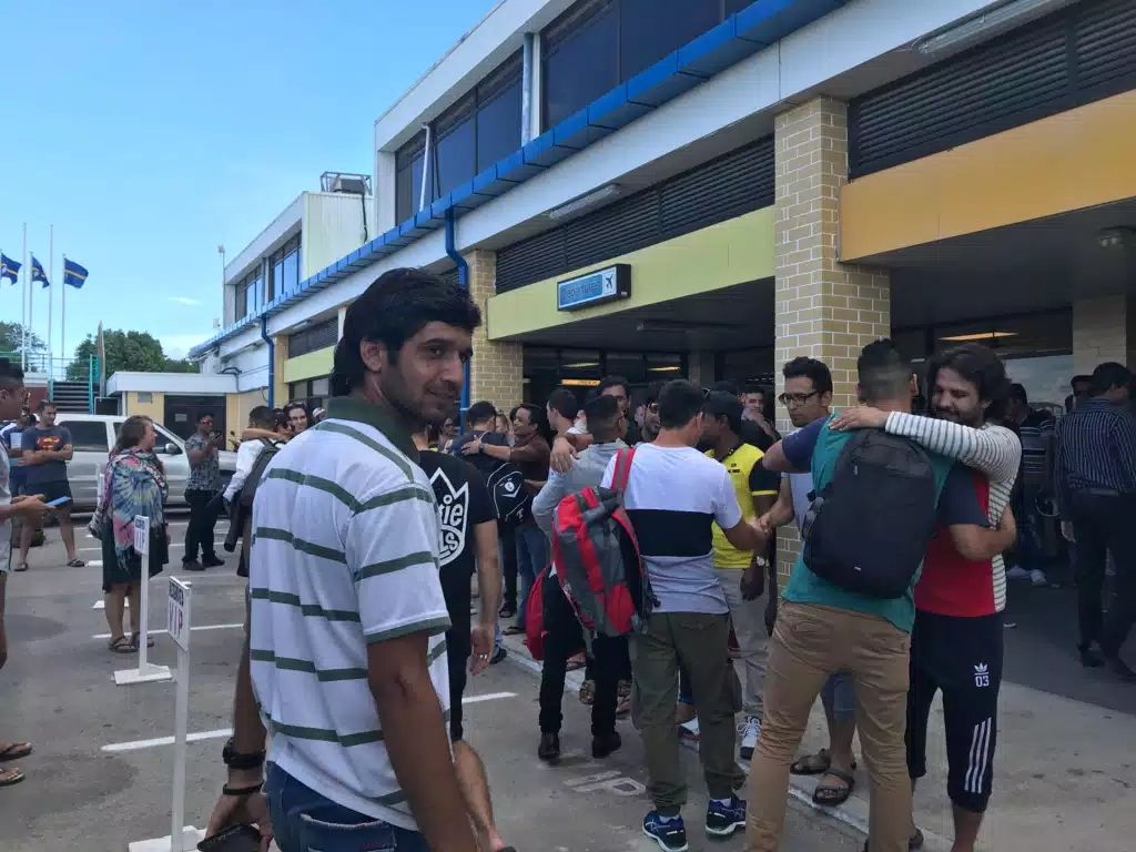 Refugees line up ahead of a transfer flight