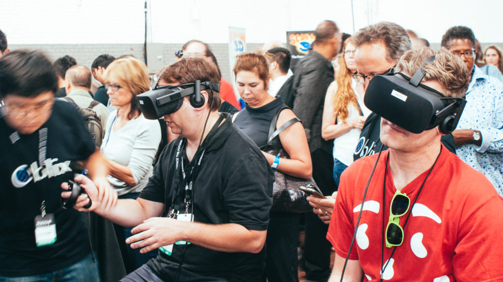 Two Worlds Fair Nano attendees enjoying Oblix's demo using Oculus Rift headsets and Oculus Touch controllers.
