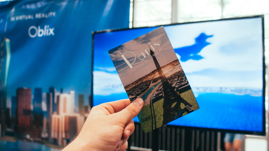 A postcard given away by Oblix with a screen capture from inside the experience.