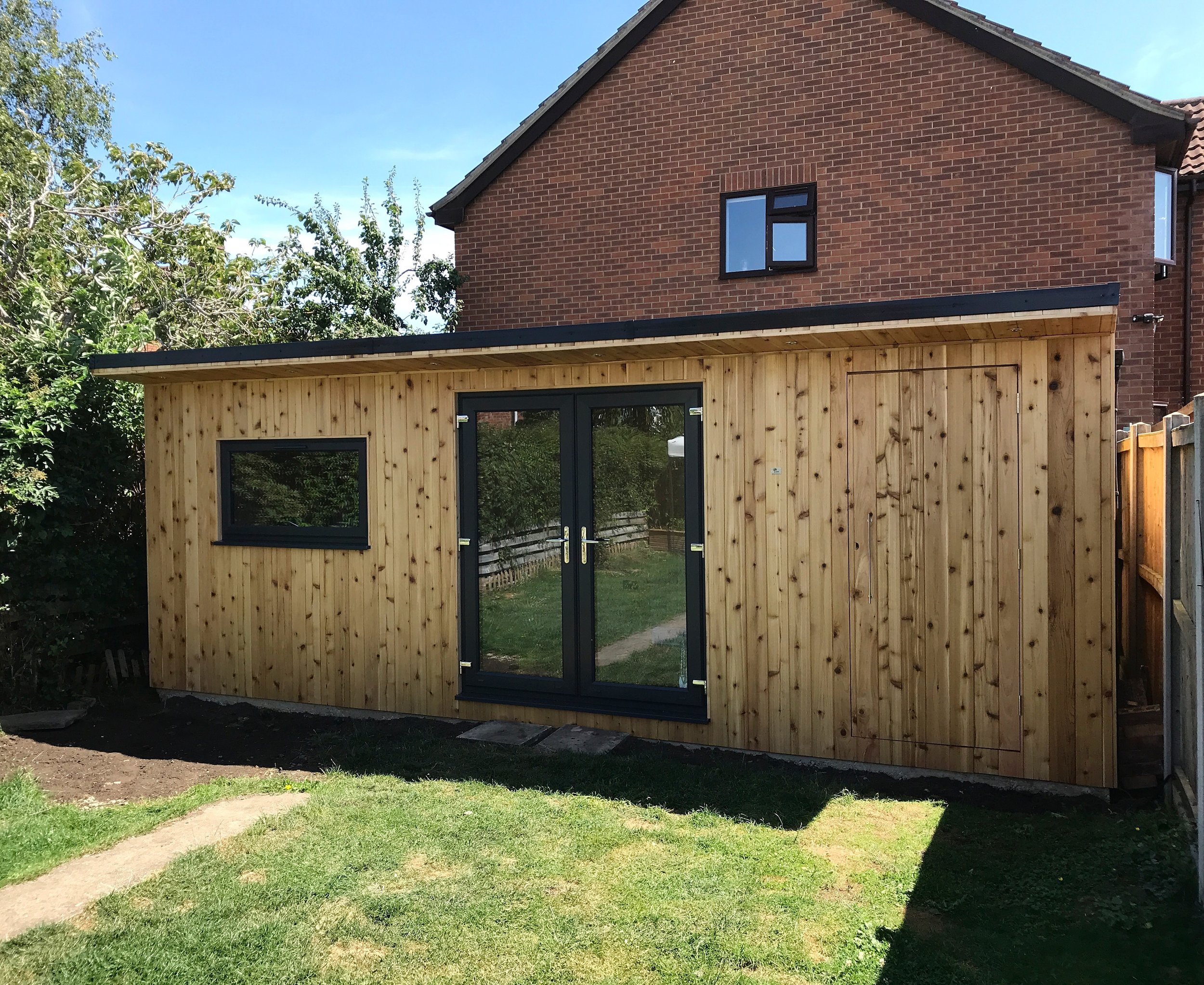 """Churchdown Garden Office - """"I literally could not recommend Rich more! I had been looking for a while at home offices as working out of a bedroom was no longer ideal. I saw a friends home office that Rich had built and asked for a quote. What we wanted was a lot bigger than anything else he had done and included a hidden shed building too.... Safe to say he absolutely smashed it out of the park. We now have an incredible home office with gorgeous red cedar cladding and a fantastic space for work (and my husband loves his new man cave shed!) Rich is friendly, professional, extremely hard working and provides gorgeous custom and bespoke work at a much better price than so many i had contacted before.From the initial quote and design images to the final product, Rich kept me updated every step of the way and it was awesome to see the progression of the build.Thank you so much again and we will be recommending you to anyone who wants a home office or outbuilding!""""Mrs Davis - Gloucestershire"""