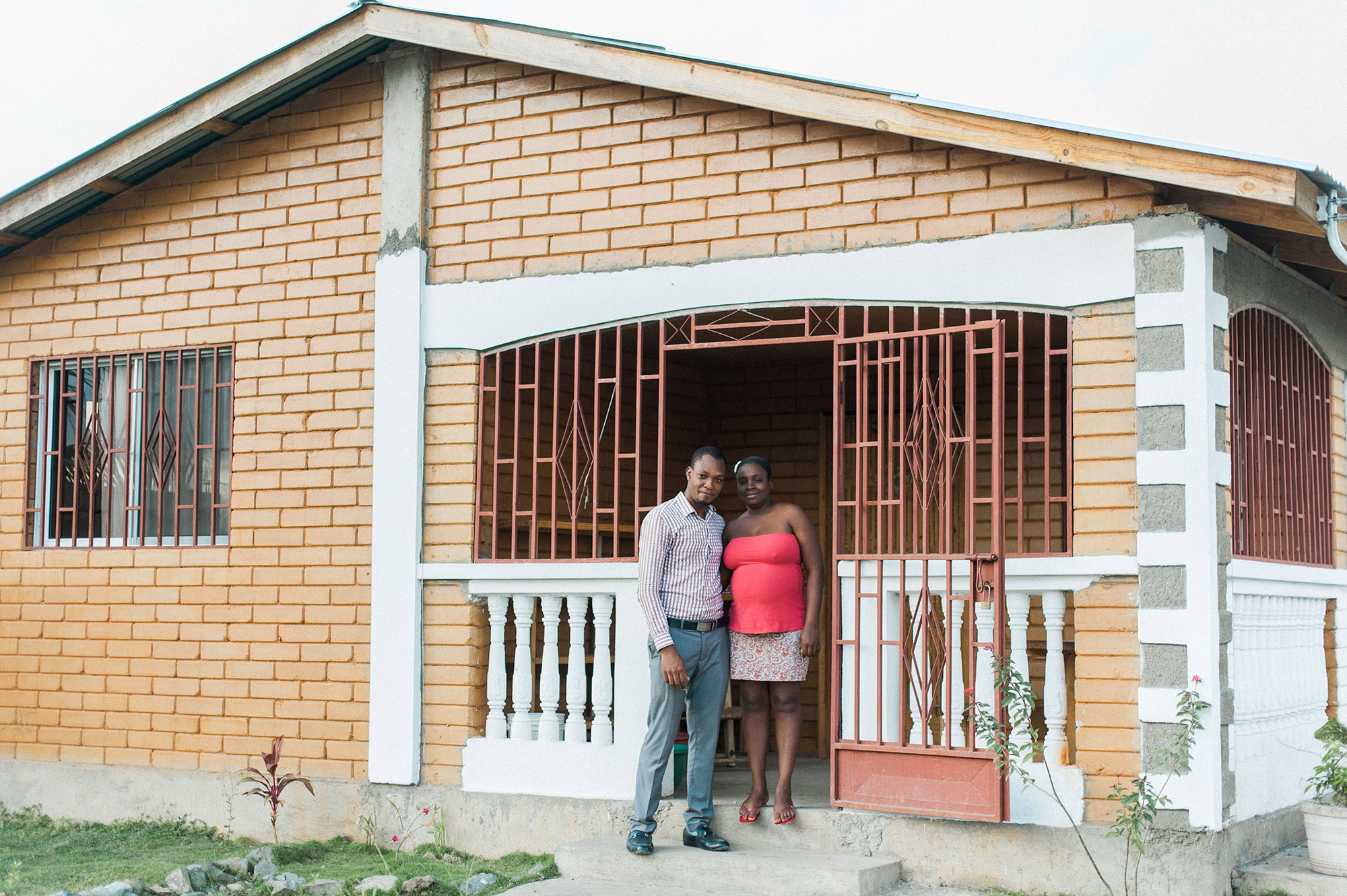 Manuacha and her husband stand on the front porch of their new earth block home, provided by PKF.