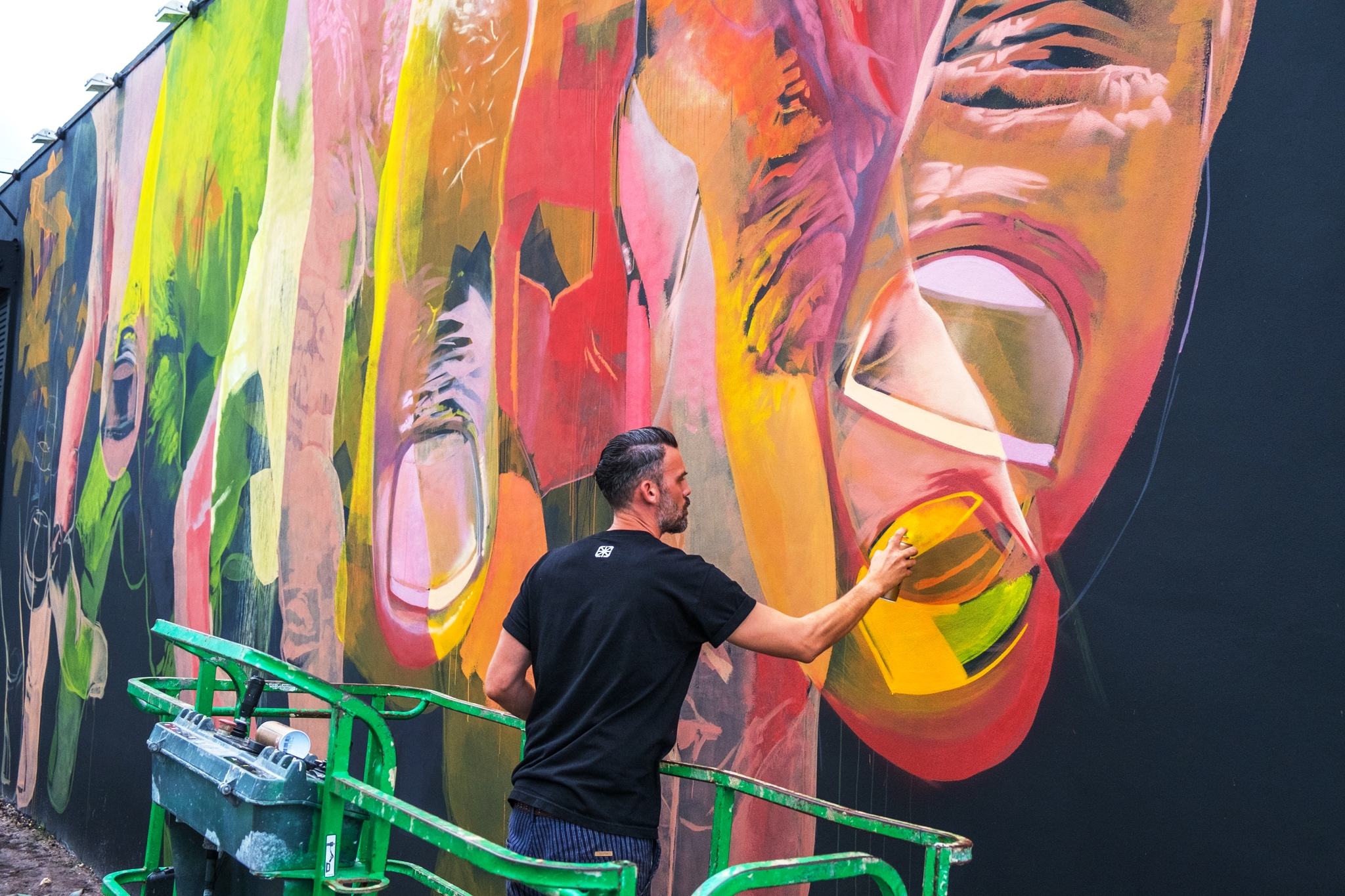CASE AT WORK ON HIS MURAL ON THE FACE OF THE GGA GALLERY