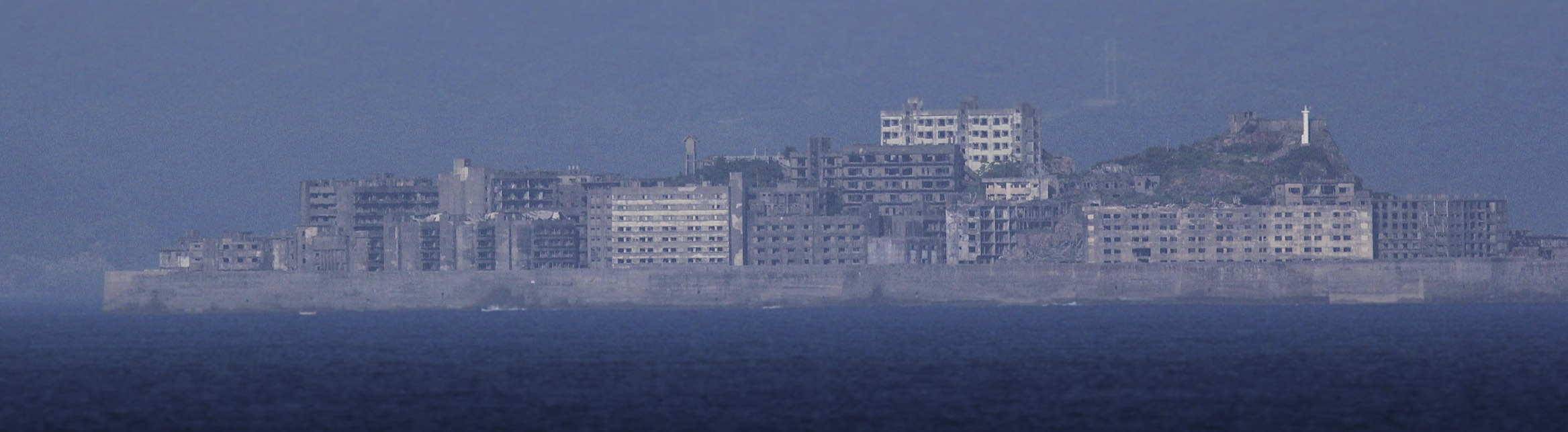 Hashima Island  is an abandoned island lying about 15 kilometers (9 miles) from the city of Nagasaki.  The island's most notable features are its abandoned concrete buildings, undisturbed except by nature, and the surrounding sea wall.