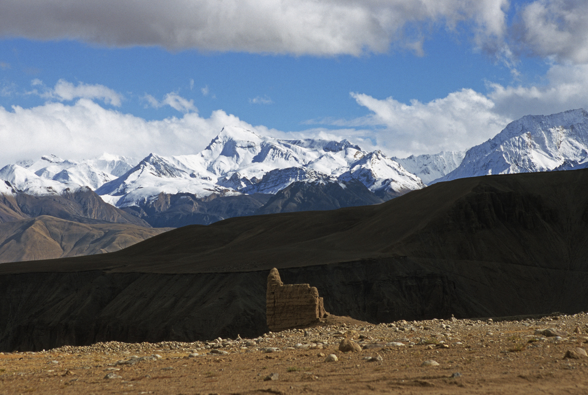 An old stupa and the Himalayas on the border with Nepal, India and China